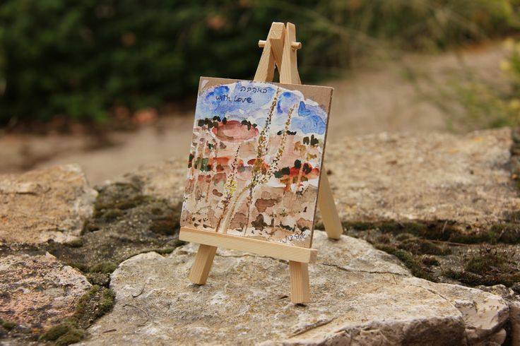 A small watercolor painting stending on a table easel