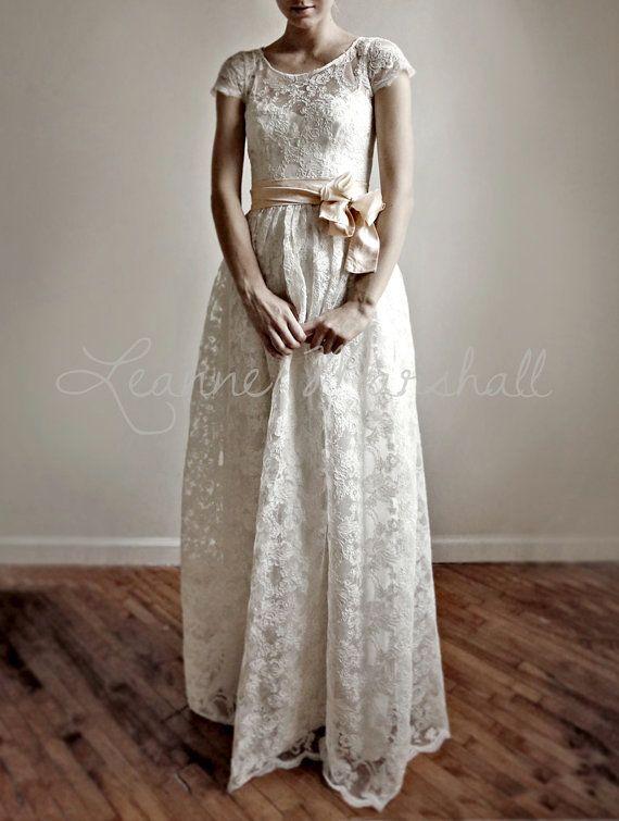Cette robe de mariée unique combine élégance moderne avec une touche vintage.    Le corps est fait dune dentelle dAlençon délicate et belle. Le corsage a un col rond, une taille ajustée et manches 1/2. La jupe est la longueur du thé.    La partie extérieure de la robe est entièrement sheer.It est livré avec une deuxième robe pour être porté sous (cette robe peut devenir plus tard une partie de votre garde-robe tous les jours. La sous robe est en coton blanc. Il est équipé par le corsage avec…
