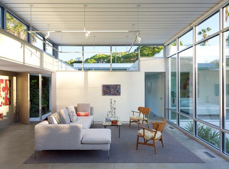 Modern Florida seaside home with b&b italia sofa, hans wegner ch22 chairs, WAC lighting co track lighting in the living room