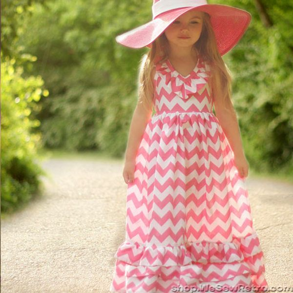 Paper sewing pattern to make a floor length girls maxi dress with ruffled halter neckline and one, two or three bottom ruffles. Violette Field Threads make this