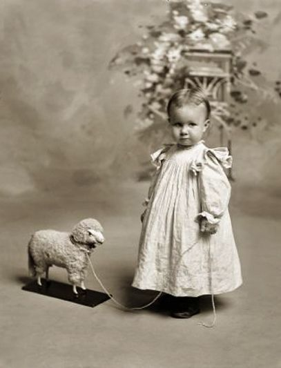 Little girl with lamb pull toy.