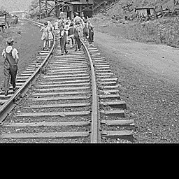 School children walk down the railroad tracks to their homes and lunches. The mine here was abandoned after an explosion in December, 1945. Four Mile, Bell County, KY. 9/4/46 - Kentucky Digital Library