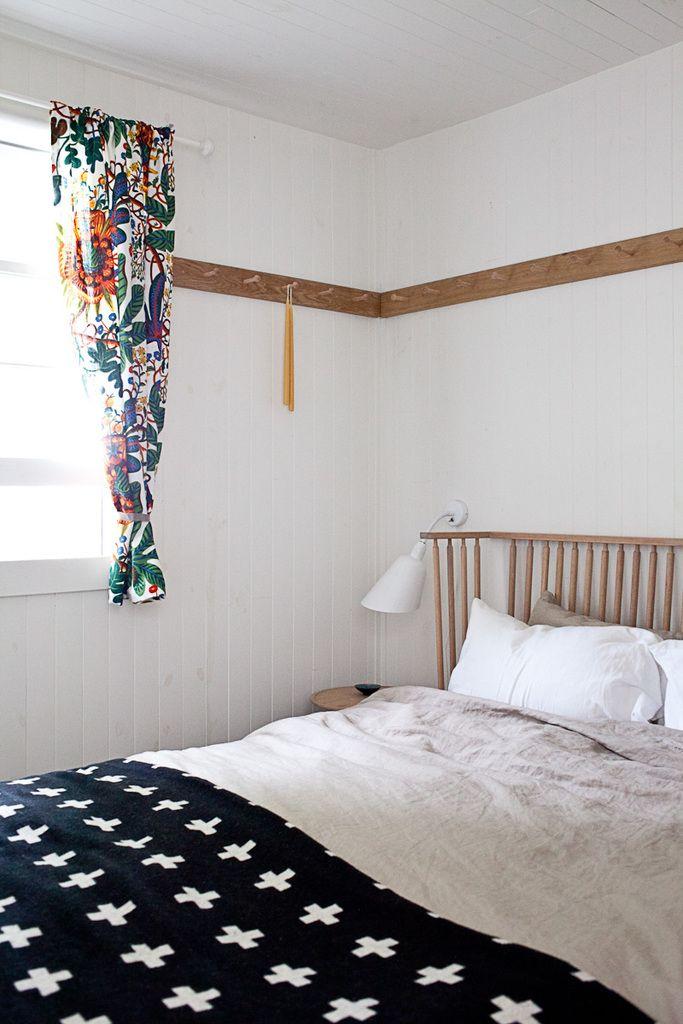 Изголовье кровати в родительской спальне повторяет дизайн спинки скамьи в столовой. Узор покрывала на кровати также выбран соответствовать скандинавскому стилю спальни. .