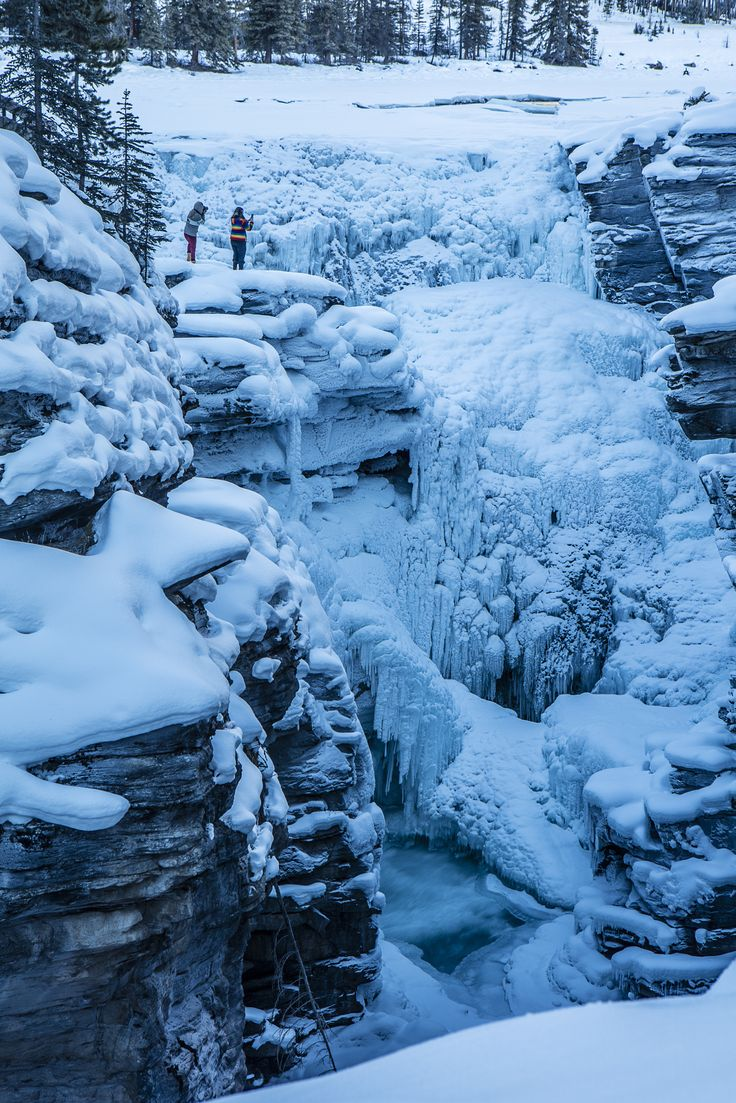 frozen selfie at the cliff sunwapta falls - I may take risks taking photos and am 5 feet from a cliff but these two think its a good idea to climb out on the ice for a selfie over a frozen waterfall with a hundred foot drop off. One slip and well........over they go!