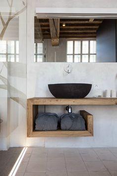 baño con lavabo negro de diseño sobre encimera y balda de madera, grifo de pared