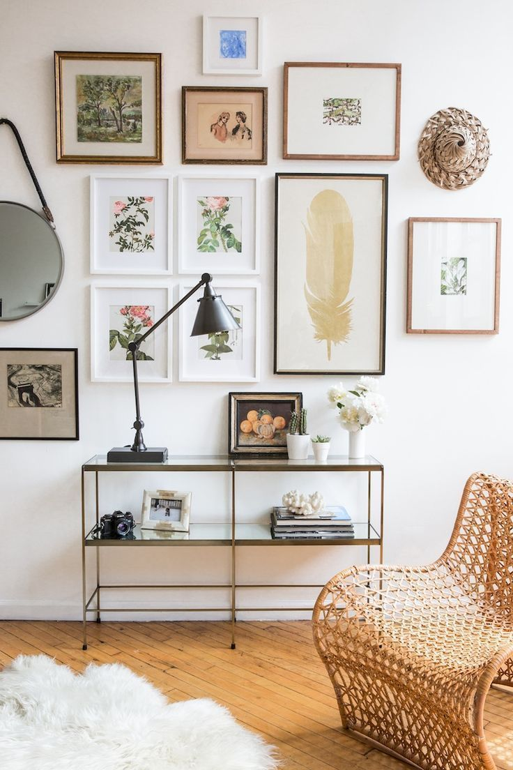 """Here's a really creative gallery wall featuring mostly botanical and nature-inspired artwork. There's a traditional grid of white framed floral art, but surrounding that rectangle, is a salon style grouping. The simple, streamlined style of the console table even looks to work as a part of the grouping, with its """"grid-like"""" structure. Many take-aways in this inspirational vignette!"""