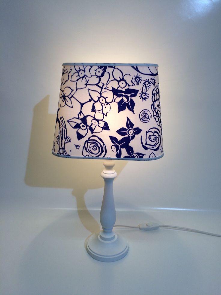 """Semplice ma elegante lampada composta da basamento in legno verniciato in bianco che sorregge una ventola trapezoidale realizzata in tessuto della collezione """"Ken Scott"""""""