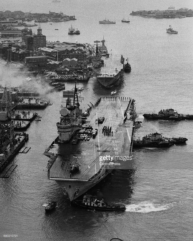 Aerial view the flight deck of the Royal Navy Audacious-class fleet aircraft carrier HMS Eagle as tugboats ease her towards the dockside of Portsmouth harbour to be paid off and scrapped on 26 January 1972 at Portsmouth, United Kingdom. The commando carrier HMS Albion is docked behind HMS Eagle. (Photo by Central Press/Hulton Archive/Getty Images).