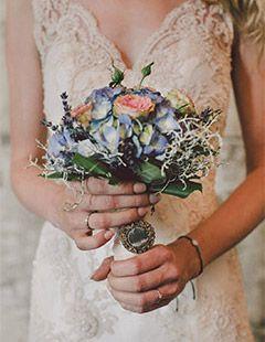 Isabell in einem wunderschönen, cremefarbenen Brautkleid aus eleganter Spitze mit einem Brautstrauss im Vintage-Stil.