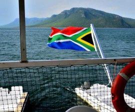 Die Flagge der Regenbogennation-Südafrika über dem Indischen Ozean.