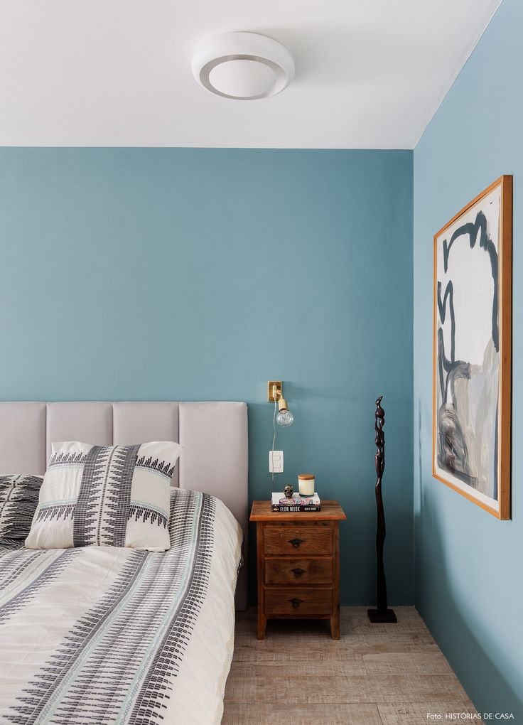 Parede pintada de azul, luminária dourada e criado mudo de madeira.