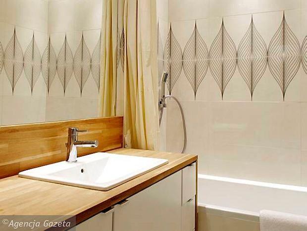 PO ZMIANIE. Szafka pod umywalką została zrobiona na wymiar z lakierowanej płyty. Pod blatem zmieściły się półki na ręczniki i środki czystości, szufladki na drobne kosmetyki oraz pralka. W wannie można swobodnie wziąć prysznic - oprócz tradycyjnej rączki prysznicowej zainstalowano w niej bowiem deszczownicę. Przed zachlapaniem wnętrze chroni  zasłonka, przesuwająca się po szynie na suficie.