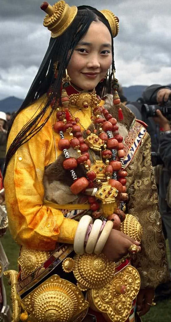 Litang Horse Race Festival 2006 | (Pinterest friendly zoom-in of previous pic) Local girl at the Litang Horse Festival dressed to the nines in her family's life savings. I've seen Chinese websites stating that the small group of women who attend(ed) Litang dressed like this each worse multiple kilograms, even tens of kg of solid gold. I'm doubtful, and think that the ornaments she wears are gilded silver, but what she is wearing is worth a fortune by any country's standards