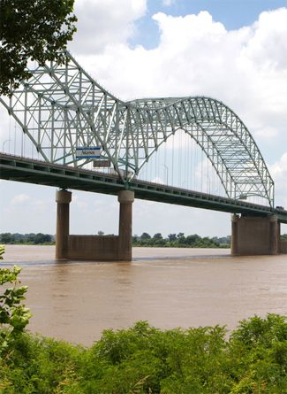 "The Memphis - Arkansas bridge or the ""M"" bridge over the muddy Mississippi River connects Memphis to Arkansas."