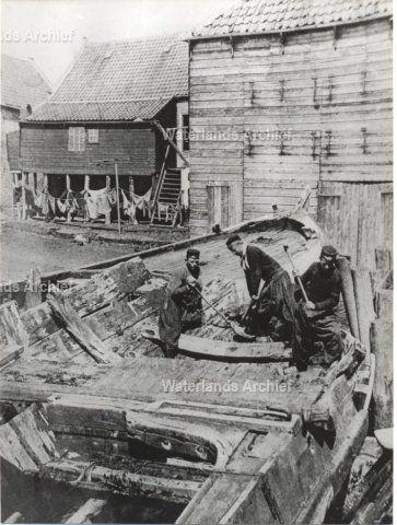 Na de aanleg van de nieuwe helling in de Zuiderhaven werd de oude helling in de Golf van Ma gebruikt als kerkhof voor de oude botters, die uit de vaart waren genomen. Hier zien we enkele mannen bezig met de sloop van een oud schip. Het vrijgekomen hout diende weer als brandstof voor de kachel thuis. Hier zien we aan de linkerkant Jan Zwarthoed 'van Boertje' (1880-1949) als bottersloper. ca 1915 #NoordHolland #Volendam