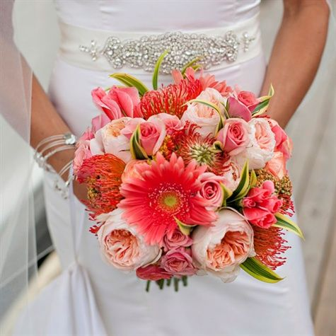 Nicki's Bridal bouquet was an elegant assortment of vibrant blossoms such as garden roses, dahlias and gerbera daisies in different shades of coral. The bouquet was wrapped in alabaster satin ribbon and fastened with crystal pins. from the album: A Coral and Turquoise Fun Wedding in Newport, RI