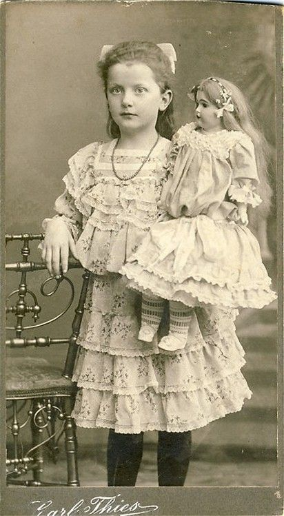 Antique photo of little girl with her doll.