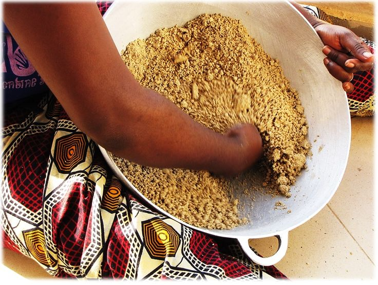 After dampening, begin hand-forming of sifted millet flour ('soungouf' in the Wolof language, and 'la farine de mil' in French) into pellets for millet recipes. A very tactile and pleasant hand-process that develops fine-motor skills.  African ethnic meals, ethnic food is everyday in Africa. ©2014 T.K. Naliaka. Robust, nutritious, inexpensive and well-balanced meals.