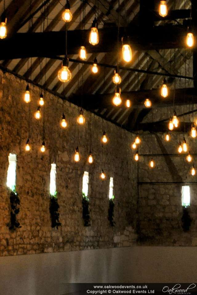 Creating a golden glow in a barn with limited natural light - stunning Edison bulb wedding lighting for modern and vintage wedding styles