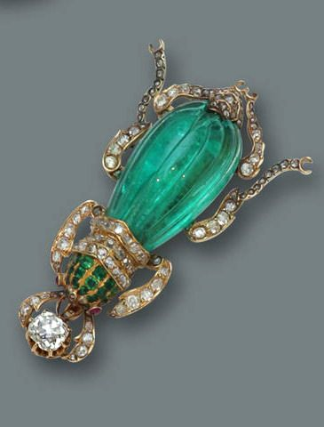 An emerald, diamond, and ruby brooch in the form of a beetle, with a fluted emerald body, old European and rose-cut diamond legs, calibré-cut emerald head and cabochon ruby eyes; estimated total diamond weight: 2.00 carats; mounted in eighteen karat gold.
