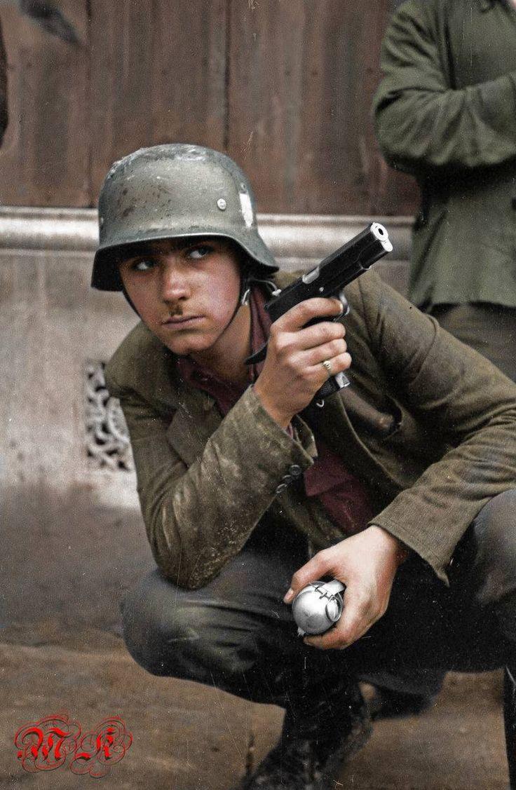 """Śródmieście Północne. Ulica Sienna w pobliżu Wielkiej. Powstaniec z pistoletem VIS i """"filipinką"""", granatem ręcznym. Zdjęcie , i opis ze zbiorów MPW."""