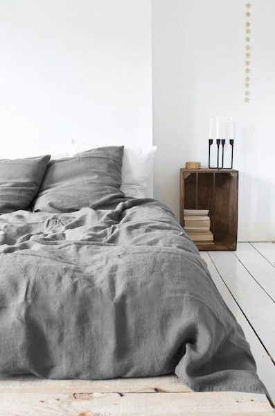 Nordic Feeling.  Gorgeous bedding and floor and side table and candles.
