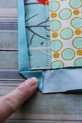 """Cheater Binding"" ~ to get that nice flat corner miters. Nice tip.  She used Rae's ""cheater binding"" method here:  http://www.made-by-rae.com/2010/10/rae-pretends-she-can-quilt-and-shares-a-quick-quilting-tutorial/"