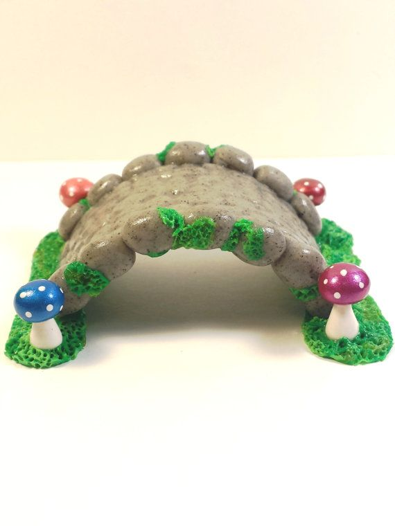 Miniature cobblestone fairy bridge. Made from granite polymer clay. Bright mushrooms colored with mica powders are at each corner of the