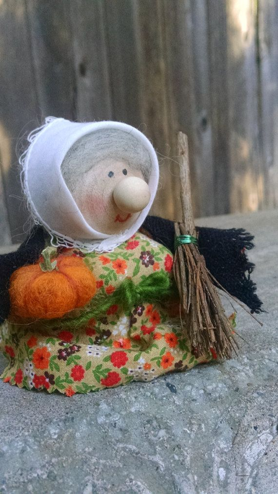 This cute little kitchen witch is constructed of wool and wool and stands about 4 inches tall. She holds a broom constructed of twigs and wire and a