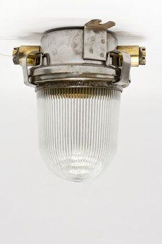 Stoere, industriële plafonniere, te dateren rond de jaren 70. Afkomstig van een (gedemonteerd) Engels marineschip. Een robuuste metalen houder met daarop een stevige glazen kap. Een tip: wil je liever het snoer niet zien lopen, boor dan een klein gaatje in de bodem van de lamp; om daar het snoer doorheen te trekken. De laaste foto, de ronde onderkant (zonder uitsteeksels), diameter: 10 cm.