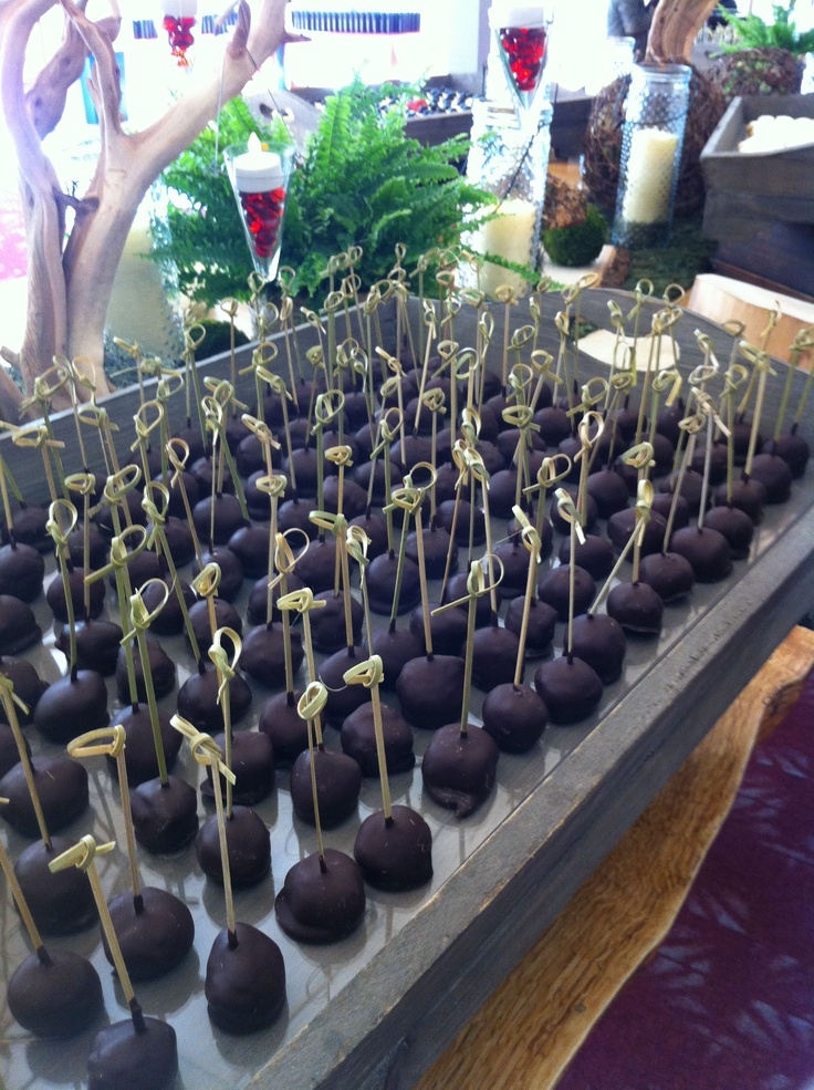 Chocolate-dipped cheesecake lollipops on knotted picks. Displayed on an acrylic-lined huge rustic wood tray.