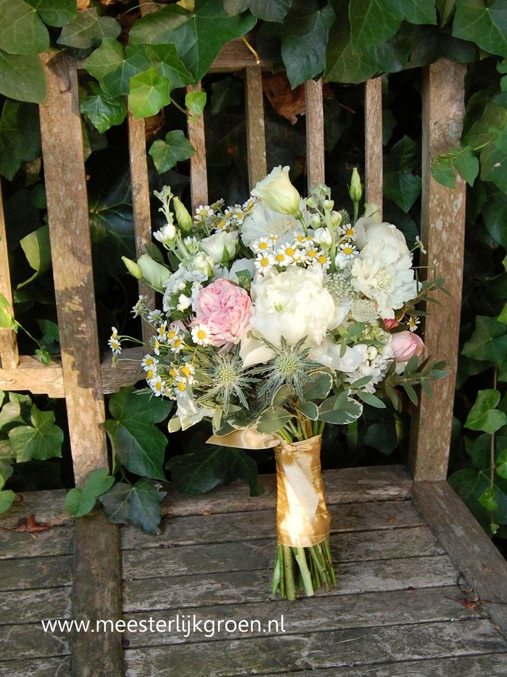 Hand gebonden bruidsboeket in veldboeket stijl. Kleuren zijn wit met een beetje zacht roze en goud. Gebruikte bloemen o.a. pioenrozen, distel, Eustoma, scabiosa, Tanacetum Victory (enkel). www.meesterlijkgroen.nl