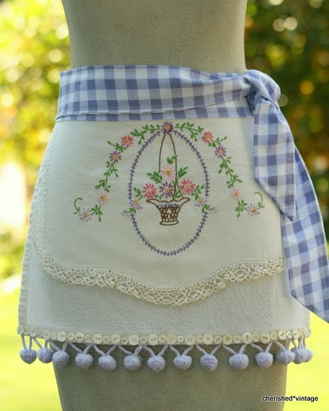 I adore this apron made with a vintage embroidered table scarf, gingham, and pom pom trim