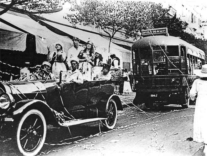Primeiros ônibus elétricos do Rio Em 1917, a prefeitura aprova a instalação de um serviço de ônibus pela Av. Rio Branco, entre a praça Mauá e o Palácio do Monroe (antigo Senado). Foram utilizados carros elétricos movidos a bateria, construídos nos Estados Unidos. Tendo sido os veículos aprovados nos testes, o serviço foi inaugurado em 1918, durando até 1928. Na imagem vemos o ônibus na avenida durante o carnaval, atrás de um grupo de foliões