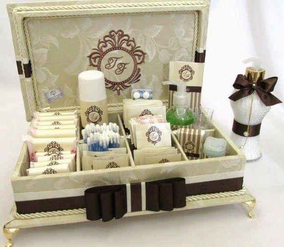 Caixa de madeira forrada de tecido adamascado marfim, com divisórias. Com bordado na tampa. Incluso itens de higiene e medicamentos com rótulos personalizados. Incluso 1 sabonete líquido decorado combinando com a decoração da caixa. Tamanho 33x25cm R$ 384,00
