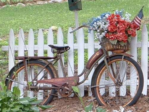 old bike with flowers on white picket fence