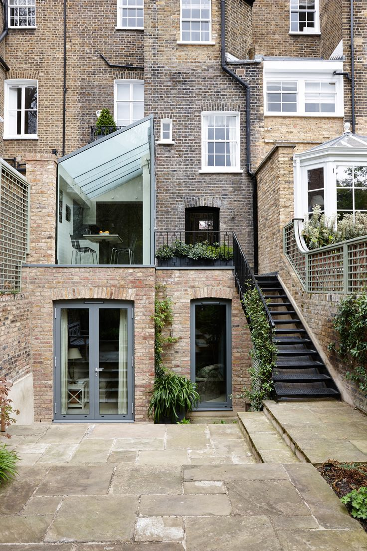 Trombe - External photo on rear side of London Home. A structurally glazed modern extension with clear glass end gable and a switchable frameless glass roof