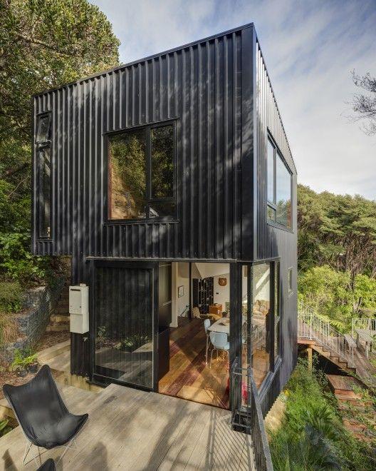 Blackpool House (Waiheke Island, NZ) / Glamuzina Paterson Architects. Simple form, stained clad exterior, weathered deck/floor + black framed windows/doors.