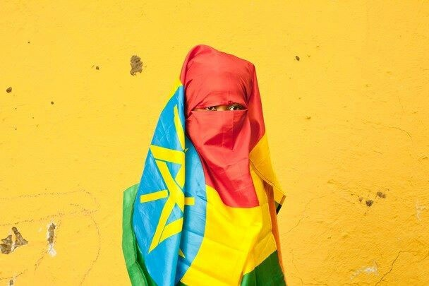 A little girl wraps herself in the Ethiopian flag.