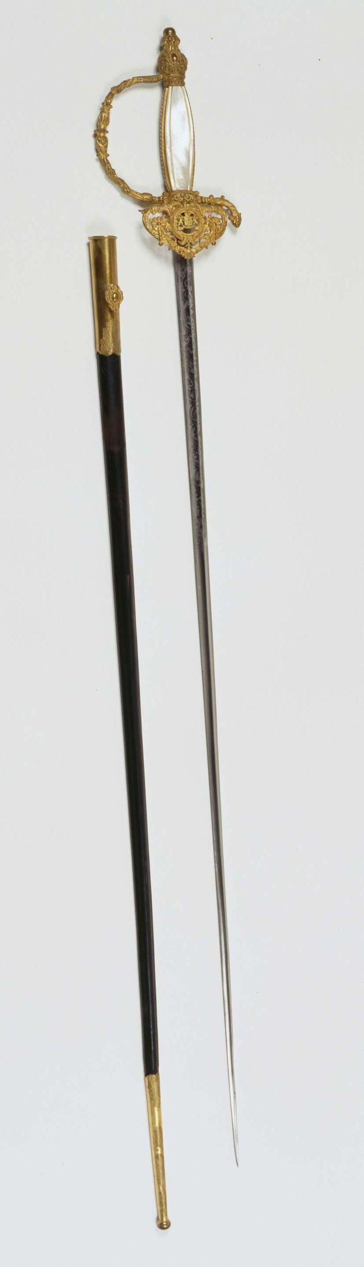 Fa. Frans Pauwels | Degen in schede en foedraal behorende bij het ambtskostuum van Dr. A.H.J. Lovink, Fa. Frans Pauwels | Degen met vuurverguld koperen gevest, opengewerkte stootplaat met o.a. guirlande en het Rijkswapen, driezijdige ijzeren geëtste kling met aan elke zijde een geul met guirlande-decoratie. Gesigneerd aan de achterzijde 'Frans Pauwels, hofleverancier te 's Gravenhage'. Aan voorbeugel: dragon of sabelkwast van gevlochten gouddraad waaraan kwast met vuurvergulde ijzeren peer…