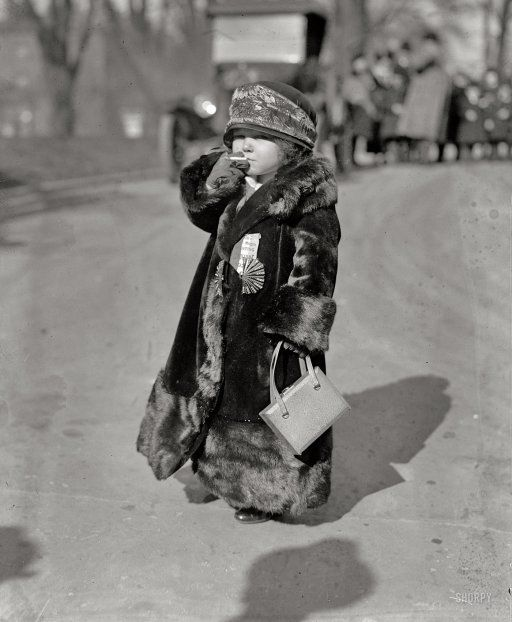 A real little it-girl wearing fur coat and cap and a mini purse.