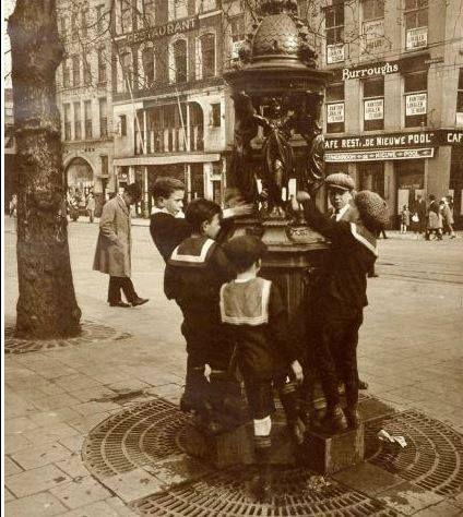 Beursplein Bij een straatfonteintje zijn vijf jongens in matrozen pakjes, met water aan het knoeien. 1925