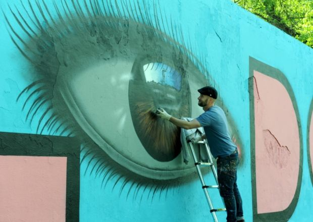 Hilsea Lido mural painting. Pictured is artist My Dog Sighs painting the eye.