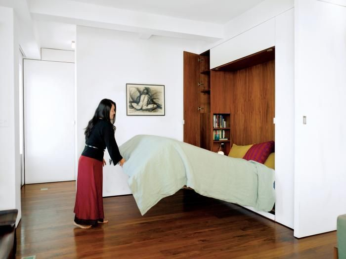 Studio Garneau, pull down murphy bed with pea green cover, white floors, wood floors and walnut lined storage