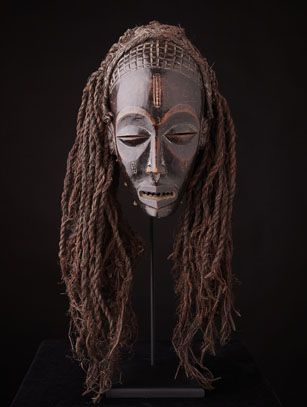 Female masks of the Chokwe people in Angola & D.R. Congo are called Mwana Pwo (young maiden) and are one of the mask types used in the Mukanda, or initiation ceremonies for young men. Although always worn by men, the mask embodies an ideal of feminine beauty, serenity and grace. The tightly fitted knit costume worn with the masks include false breasts. Mwana Pwo represents the female ancestor, and in a performance, is meant to import fertility to the spectators. The gestures of the dancer…