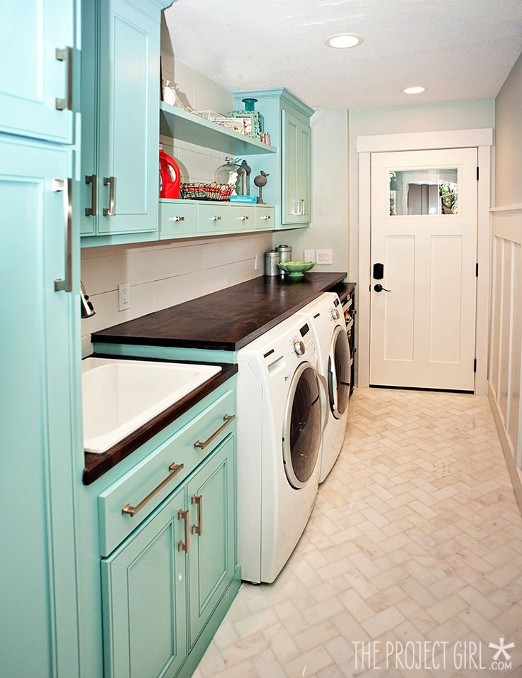 Laundry room: Fun aqua cabinets, wood counter and herringbone marble floor.