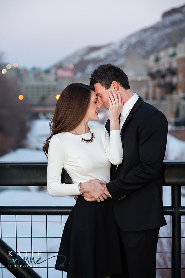 Lovely black skirt and handsome black tie suit on the snowy streets of Golden Colorado's downtown.  Coors Brewery in the background.  Engagement session photos by Katie Corinne Photography.  Romantic, elegant and intimate.