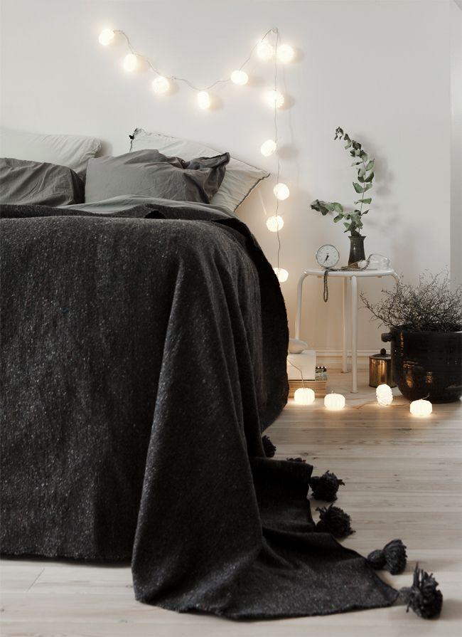 Love the romantic spirt of the dark grey bed and lights. Cosy bedroom.