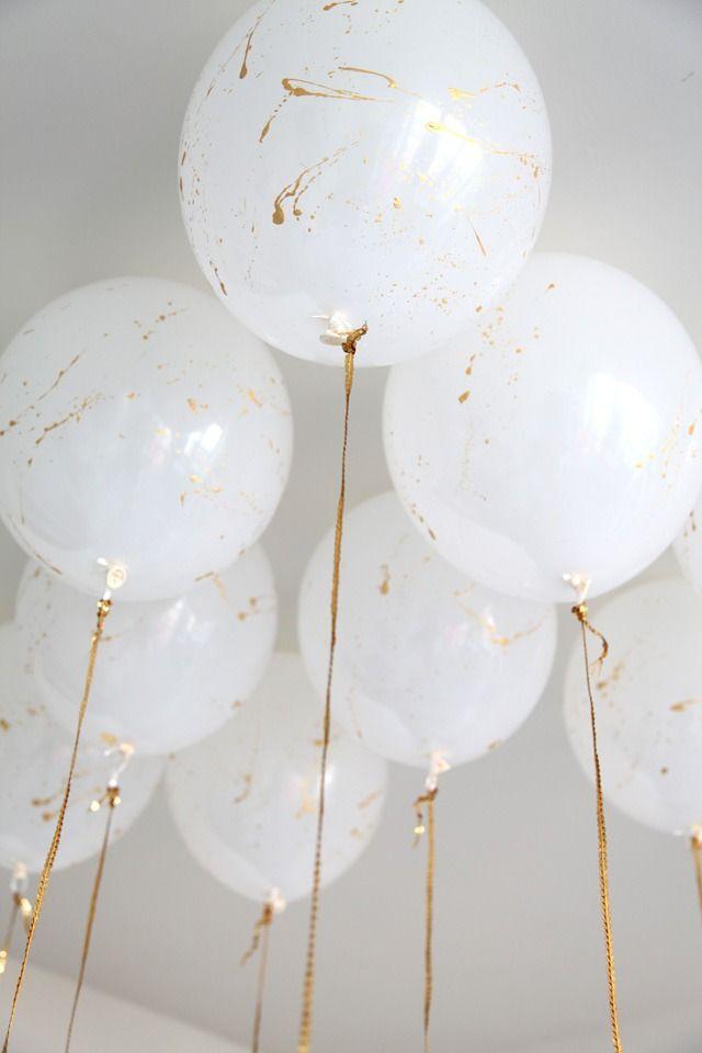 Gold splattered white balloons.