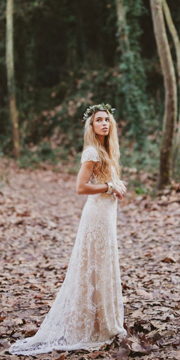 Bohemian bridal style with lace gown and flowers in hair.